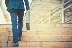 Business man holding a briefcase walking up the stairs in the routine of working with determination and confidence.