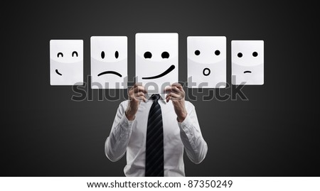 Business man holding a card with smiling face. Man chooses an emotional faces. On a black background