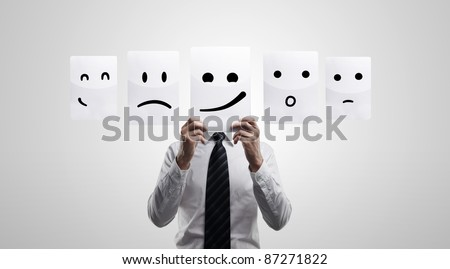 Business man holding a card with smiling face. Man chooses an emotional faces. On a gray background
