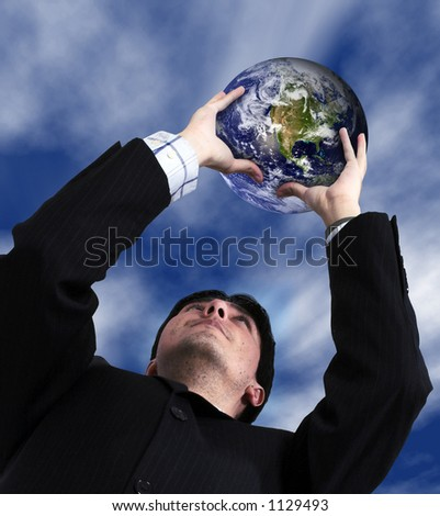 business man holding a globe up with the sky in the background