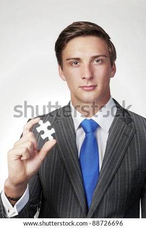 business man holding a jigsaw piece in his hand