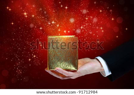 Business man holding a magic box on red shiny background - stock photo