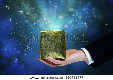 Business man holding a magic box on shiny blue background