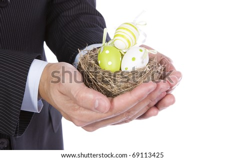 Business man holding a nest with many colorful easter eggs