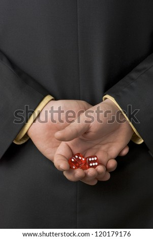 Business man holding a pair of dice behind his back preparing for the chance of a lifetime