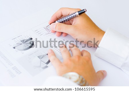 Business man holding a pen in hand analyzing graph and making notes - stock photo