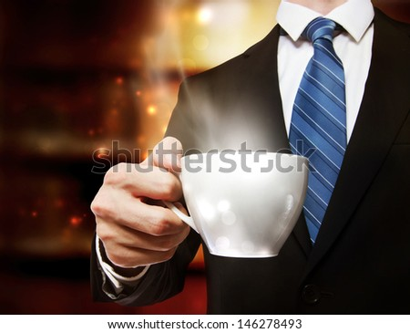 Business man holding a steaming cup of hot coffee