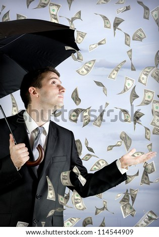 Business man holding an umbrella, money falling from the sky