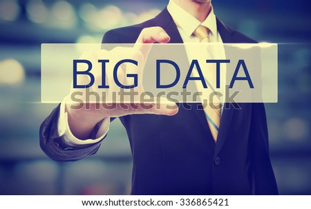 Business man holding Big Data on blurred abstract background
