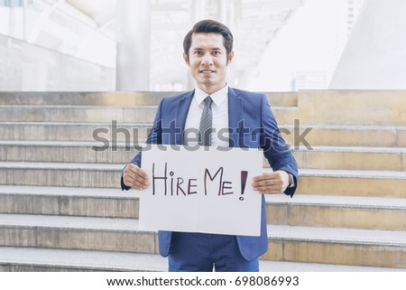 business man holding  board with text hire me on business district , business concept