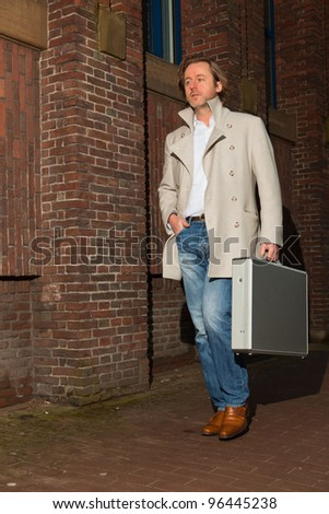 Business man holding briefcase walking on the street. Long hair wearing white coat and jeans.