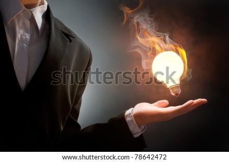 Business man holding fire light bulb