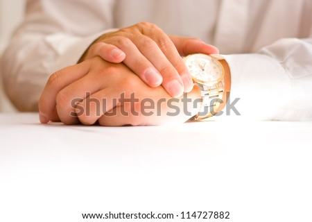 Business man holding hands folded on a table watching on his watch - stock photo