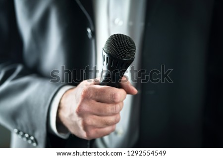 Business man holding microphone. Public speaking and giving speech in suit for audience concept. Fiance, host or best man giving toast with mic in wedding. Karaoke, talent show or singing contest. Stock photo ©