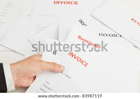 Business man holding numerous invoices and reminders