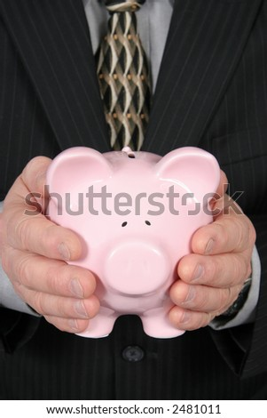 Business man holding Piggy Bank in front of him taken closeup
