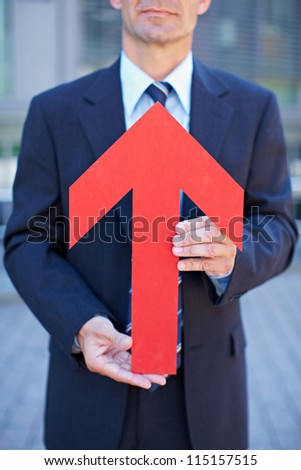 Business man holding red arrow pointing towards his face