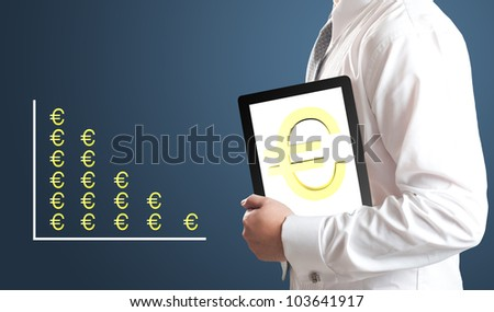 Business man holding tablet PC with Euro currency sign on screen with Euro currency chart in background. Concept for Europe economic crisis.