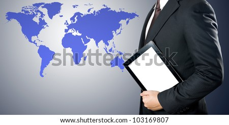 Business man holding tablet PC with world map background