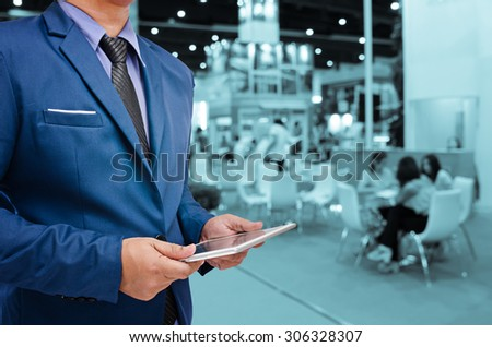 business man holding tablet with blurry event background