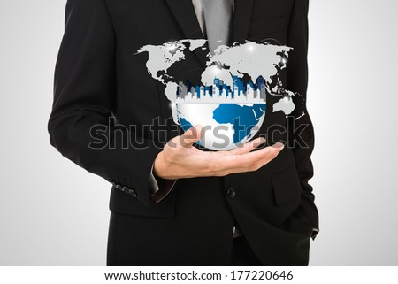 Business man holding the small world of city in his hand