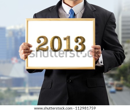 Business man holding white board Wood letter 2013
