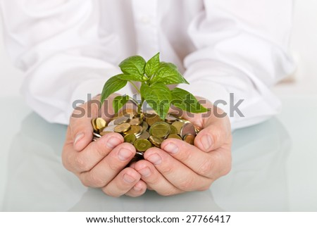 Business man holding young plant rising from a pile of coins - good investment and savings concept