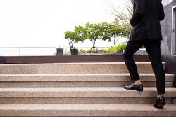 Business man in a black suit and leather shoes walking up the stairs with blank space for adding text.