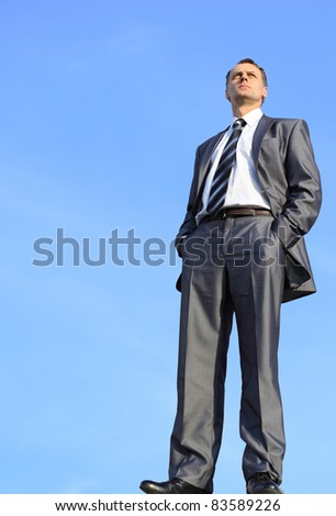 business man in a blue shirt against the blue sky. a symbol of leadership, success and freedom.