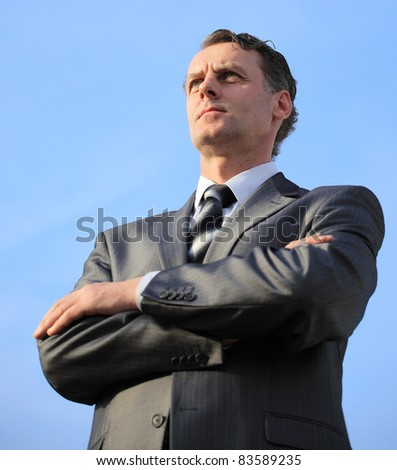 business man in a blue shirt against the blue sky. a symbol of leadership, success and freedom. - stock photo
