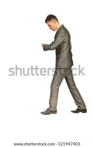 Business man in a hurry walking at work and checking time isolated on white background