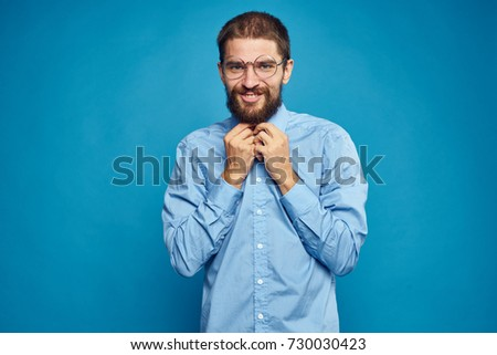 business man in a shirt with a beard smiling on a blue background