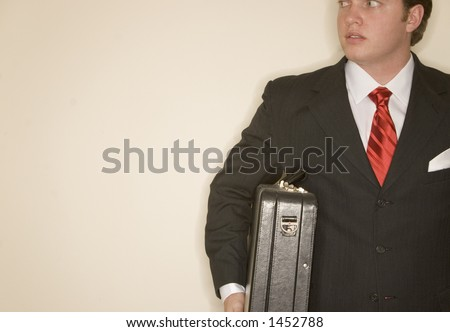 Business Man In Black Suit, White Shirt, And Red Tie Holding