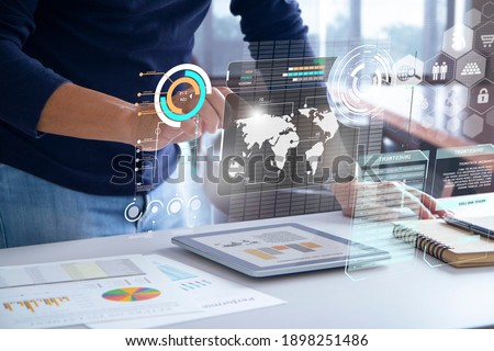 Business man in blue casual costume touching futuristic augmented reality touch screen while analysing business information on performance, investment risk or return on investment