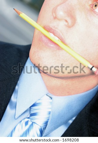 Business man in blue shirt is biting down on yellow pencil as he looks away - stock photo