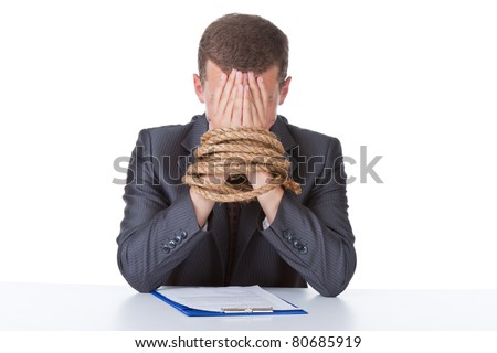 Business man in elegant suit sitting at desk tied hands cover face by hands with rope concept. Isolated over white background.