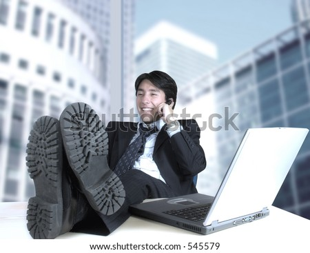 business man in his office talking on the phone with a corporate view through the window