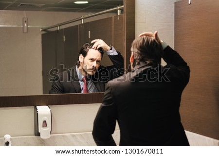 Business man in office bathroom. Stressed manager using restrooms, washroom and lavatories while looking at receding hairline. Male beauty in public toilet with businessman checking hair loss