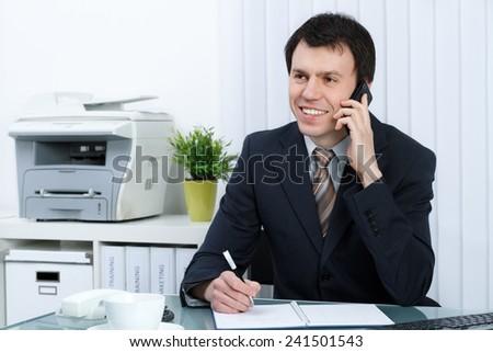 business man in office speaks on telephone