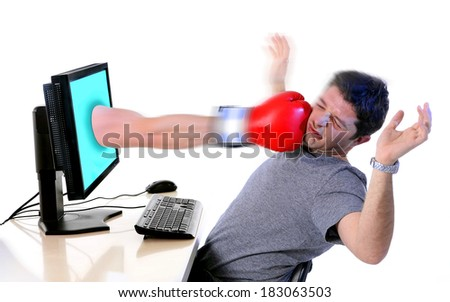 Business man in office with computer hit by boxing glove comming out of monitor  in overwork, frustration, stress and crisis concept isolated on white background