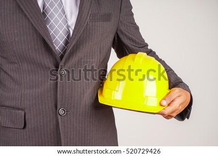 Business man in suit holding yellow safety helmet