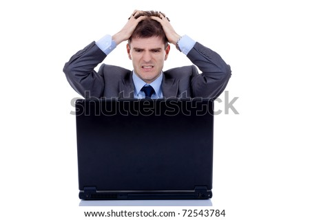 business man is frustrated on a table with a laptop, pulling his hair - stock photo