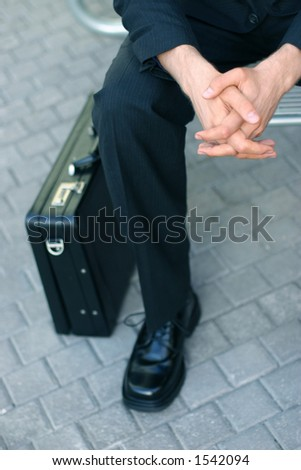 Business man is sitting down next to briefcase holding his hands