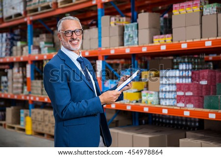 Business man is smiling during his work in a warehouse