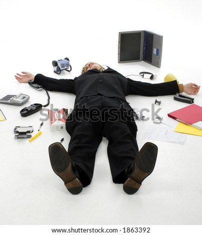 Business man laying on floor surrounded by office supplies.