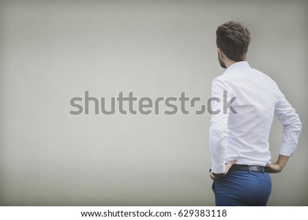 Business man looking at a empty light yellow wall. Copy space #629383118