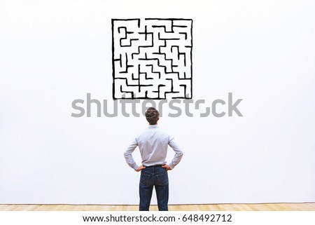 business man looking at labyrinth drawing, complicated difficult solution concept