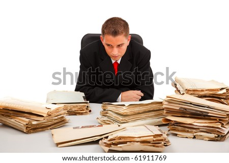 Business man looking at the huge amount of documents on table