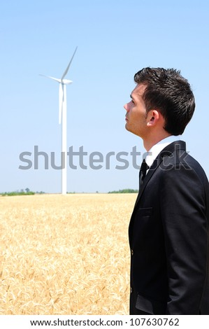 Business man looking at wind farm