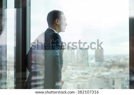 Business man looking out through the office balcony seen through glass doors.